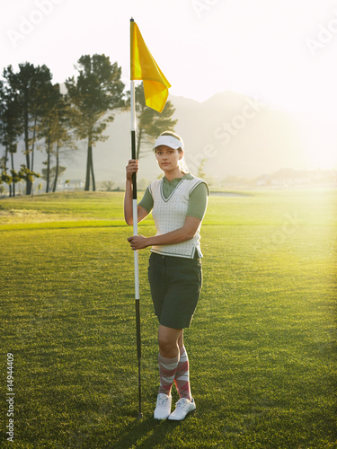 Young female golfer holding flag, portrait