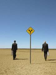 Two businessmen with briefcases walking past road sign in desert, back view