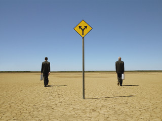 Two businessmen with briefcases in desert, back view, road sign in foreground