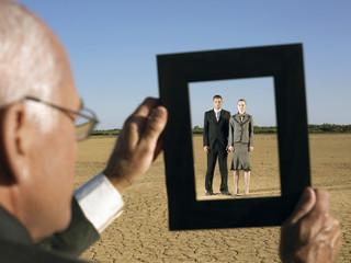Businessman framing couple in desert