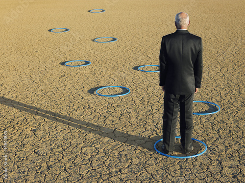 Businessman standing in hoops in desert, back view, full length