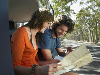 Young couple looking at map, sitting in open camper van at side of road