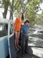Young woman standing in camper van door, man looking at map, at side of road