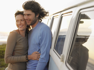 Young couple embracing by van parked by ocean, half length