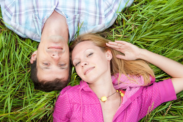Young love couple lay on the green grass outdoors.