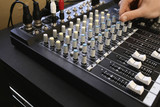 Man adjusting knob on mixing console, close-up.