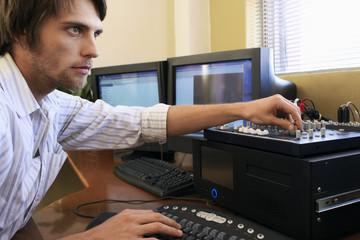 Man using computer keyboard and adjusting knob on mixer.