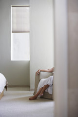 Woman sitting on armchair in bedroom, low section