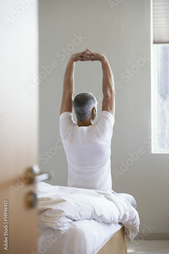 Man stretching, sitting on edge of bed, back view