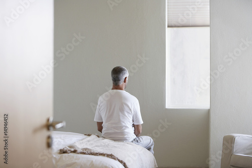 Man sitting on edge of bed, back view
