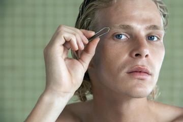 Man plucking eyebrows, close-up