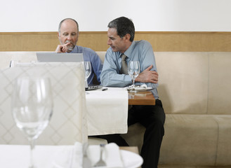 Businessmen using laptop in restaurant