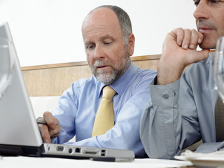 Businessmen using laptop, indoors