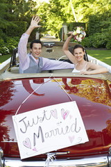 Mid adult bride and groom in retro car, waving hands