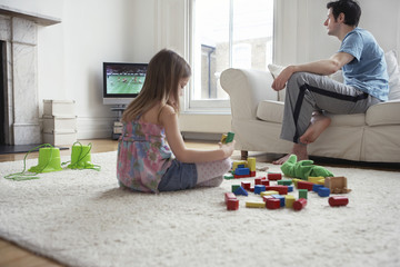Girl 5-6 sitting on floor, playing with blocks, father watching television