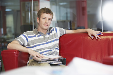 Male office worker sitting on sofa in office, portrait