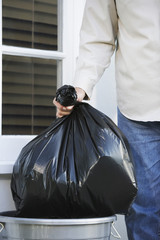 Man putting garbage bag into trash can, mid section
