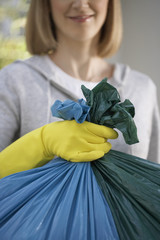 Woman wearing rubber gloves, holding garbage bag, close-up