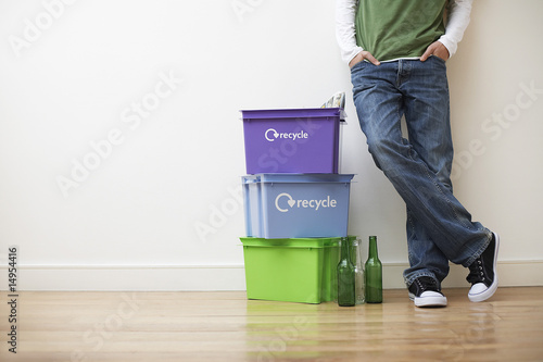 Low section view of young man leaning against wall next to small pile of recyling containers