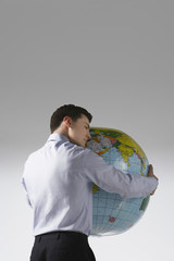 Young adult man with arms around big globe, back view