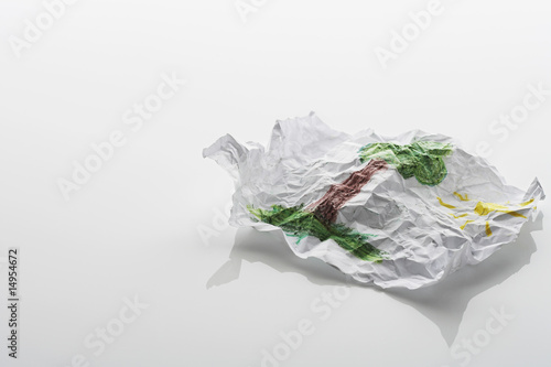 Crumpled sheet of paper with drawing of tree and sun