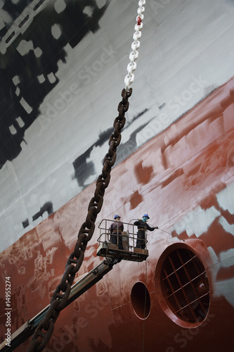 Two men in cherry picker working at ship in dry dock, low angle view