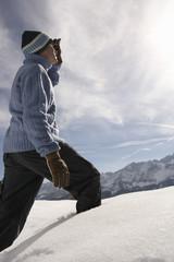 Man walking in fresh snow, side view