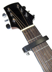 guitar neck fitted with capo on white background