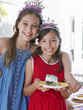 Portrait of two girls 7-9, 10-12 in tiaras, one holding plate with cake, smiling