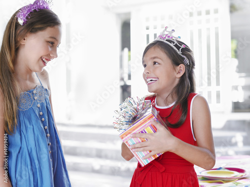 Two girls 7-9, 10-12 at birthday party, one holding present, smiling