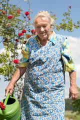 Ältere Frau giesst ihr Blumen