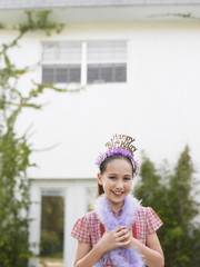 Girl 10-12 in tiara and feather boa standing outside house
