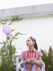 Girl 10-12 in feather boa holding balloon outside house