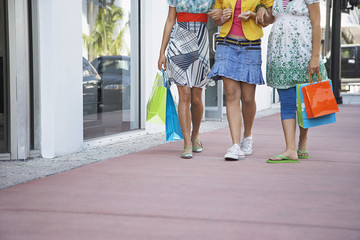 Three teenage girls 16-17 carrying shopping bags, walking on street, low section