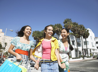 Three teenage girls 16-17 carrying shopping bags, walking on street