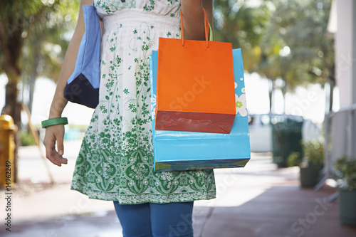 Teenage girl 16-17 carrying shopping bags, walking on street, mid section