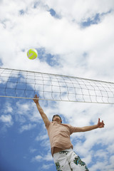 Teenage boy 16-17 playing volleyball, low angle view