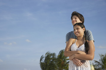 Teenage couple 16-17 embracing on beach