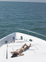 Young woman in bikini sunbathing on yacht, elevated view