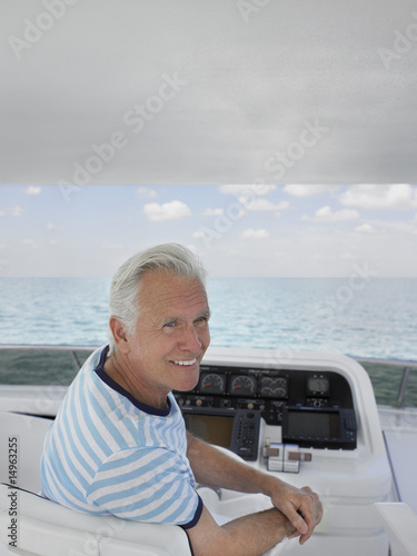 Middle-aged man sitting at helm of yacht, smiling