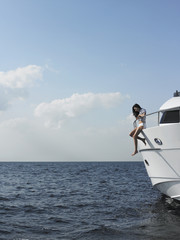 Young woman sitting at edge of yacht with legs dangling overboard, side view