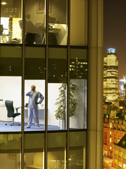 Man wearing pajamas standing in office and yawning, view from building exterior