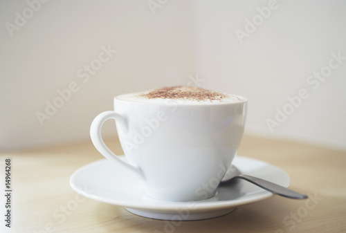 White cup of cappuccino on wooden table, close-up