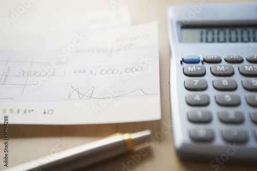 Calculator, pen and filled cheque on table, close-up
