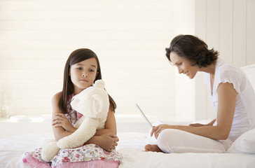 Mother using laptop, daughter cuddling teddy, sitting on bed