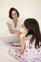 Mother using lap top, handing daughter teddy bear, sitting on bed