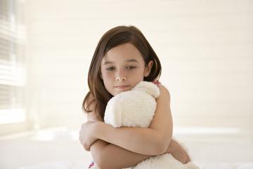 Girl cuddling teddy bear, sitting on bed, half length