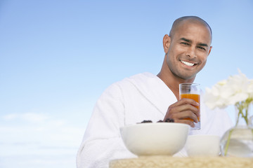Man in bathrobe with glass of juice behind breakfast table