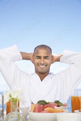 Man in bathrobe with hands behind head sitting at breakfast table