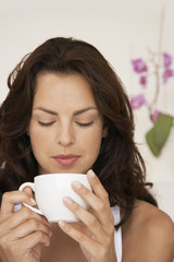 Woman drinking cup of tea, head and shoulders